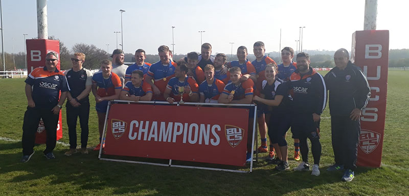Picture of Rugby Union team behind a banner that says champions