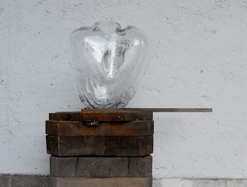 A picture of a piece of art made from glass standing on a plinth. The glass is shaped roughly like a human heart.
