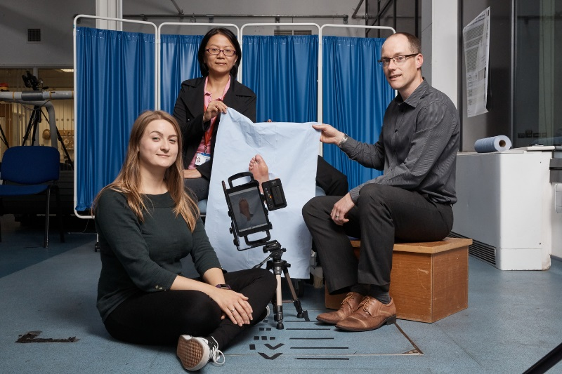 PhD researcher Katie Chatwin, left; Dr Moi Hoon Yap, Senior Lecturer in Computer Science, centre; and Professor Neil Reeves, Professor of Musculoskeletal Biomechanics, right, demonstrating the innovative FootSnap app that helps GPs take consistent photos of diabetics' feet