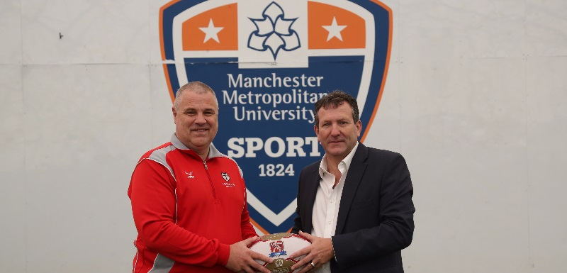 Representatives from Manchester Metropolitan University and Toronto Wolfpack pose with a rugby ball in front of the MMU Sport logo